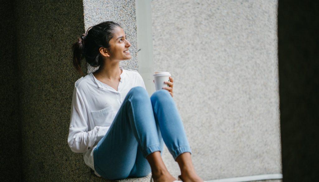 窓際に座る白いTシャツ姿の女性